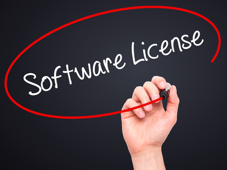 linker: Man Hand writing Software License with black marker on visual screen. Isolated on black. Business, technology, internet concept.