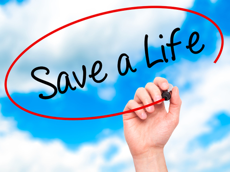 t bar: Man Hand writing Save a Life  with black marker on visual screen. Isolated on sky. Business, technology, internet concept. Stock Photo