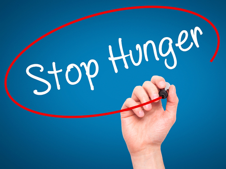 Man Hand writing  Stop Hunger with black marker on visual screen. Isolated on background. Business, technology, internet concept. Stock Photo