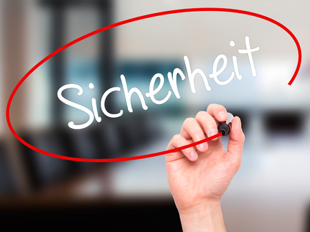 sicherheit: Man Hand writing Sicherheit (Safety in German) with black marker on visual screen. Isolated on office. Business,  internet concept. Stock Photo Stock Photo
