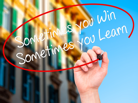 capable of learning: Man Hand writing Sometimes you Win Sometimes you Learn  with black marker on visual screen. Isolated on city. Business, technology, internet concept. Stock Photo Stock Photo