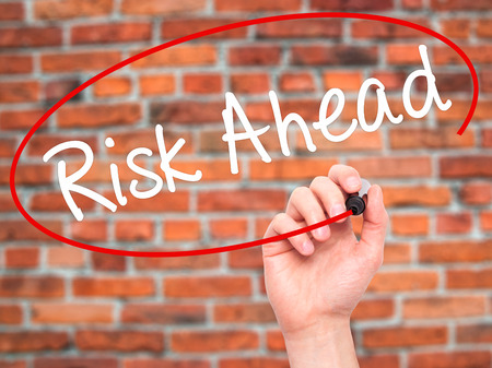 risk ahead: Man Hand writing Risk Ahead with black marker on visual screen. Isolated on bricks. Business, technology, internet concept. Stock Image