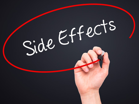 Man Hand writing Side Effects with black marker on visual screen. Isolated on black. Business, technology, internet concept. Stock Photo Imagens