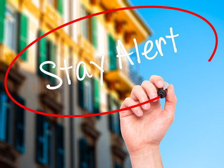 stay alert: Man Hand writing Stay Alert with black marker on visual screen. Isolated on city. Business, technology, internet concept. Stock Photo