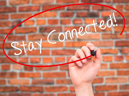 Man Hand writing Stay Connected! with black marker on visual screen. Isolated on bricks. Business, technology, internet concept. Stock Photo