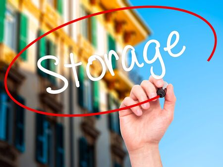 storage: Man Hand writing Storage with black marker on visual screen. Isolated on city. Business, technology, internet concept. Stock Photo