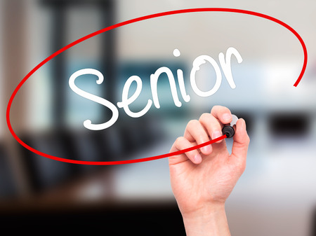 brain aging: Man Hand writing Senior with black marker on visual screen. Isolated on background. Business, technology, internet concept. Stock Photo
