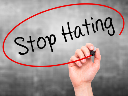 bigotry: Man Hand writing Stop Hating  with black marker on visual screen. Isolated on background. Business, technology, internet concept. Stock Photo Stock Photo