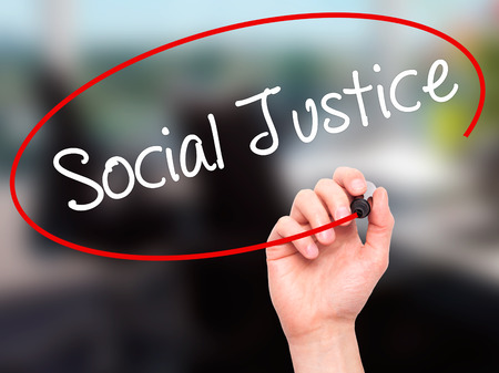 race relations: Man Hand writing Social Justice with black marker on visual screen. Isolated on office. Business, technology, internet concept. Stock Photo