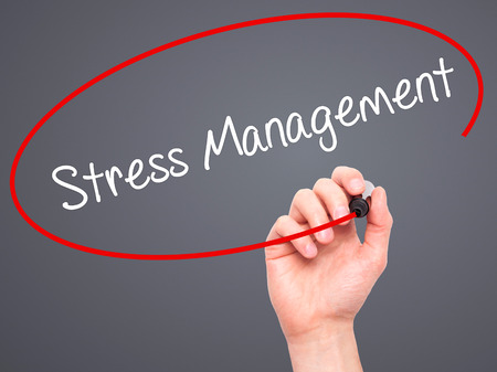 stressing: Man Hand writing Stress Management with black marker on visual screen. Isolated on grey. Business, technology, internet concept. Stock Photo Stock Photo