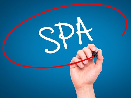 rejuvenate: Man Hand writing SPA with black marker on visual screen. Isolated on blue. Business, technology, internet concept. Stock Photo