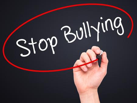 workplace harassment: Escritura de la mano del hombre Stop Bullying con marcador negro en la pantalla visual. Aislado en negro. Negocios, la tecnología, el concepto de internet. Foto de stock