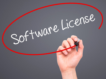 linker: Man Hand writing Software License with black marker on visual screen. Isolated on grey. Business, technology, internet concept. Stock Photo
