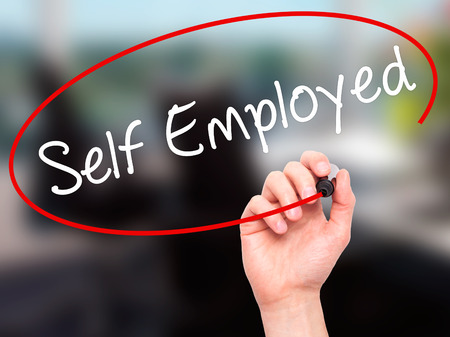 self employed: Man Hand writing Self Employed with black marker on visual screen. Isolated on office. Business, technology, internet concept. Stock Photo Stock Photo