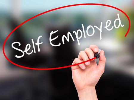Man Main Self Employed écrire avec un marqueur noir sur l'écran visuel. Isolé sur le bureau. Affaires, technologie, internet concept. photo