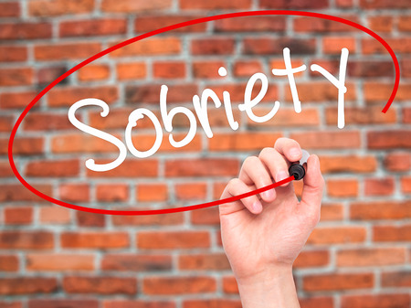 sobriety: Man Hand writing Sobriety with black marker on visual screen. Isolated on bricks. Business, technology, internet concept. Stock Photo Stock Photo