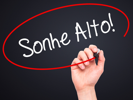 Man Hand writing Sonhe Alto! (Dream Big in Portuguese) with black marker on visual screen. Isolated on black. Business, technology, internet concept. Stock Photo Imagens