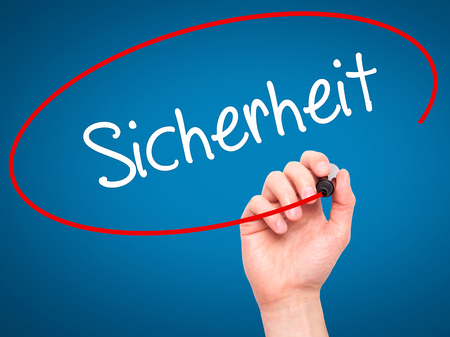 sicherheit: Man Hand writing Sicherheit (Safety in German) with black marker on visual screen. Isolated on blue. Business,  internet concept. Stock Photo