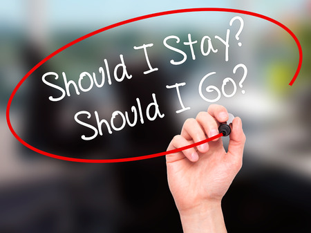 Man Hand writing Should I Stay? Should I Go? with black marker on visual screen. Isolated on office. Business, technology, internet concept. Stock Photo Stock Photo