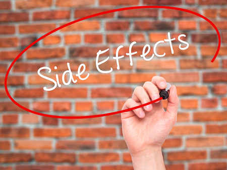 adverse reaction: Man Hand writing Side Effects with black marker on visual screen. Isolated on bricks. Business, technology, internet concept. Stock Photo