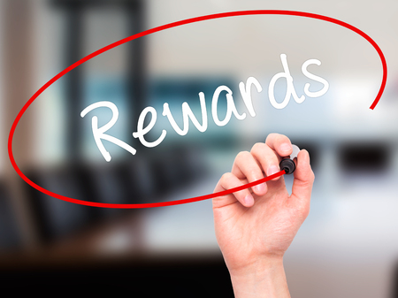 eminence: Man Hand writing Rewards with black marker on visual screen. Isolated on office. Business, technology, internet concept. Stock Photo Stock Photo