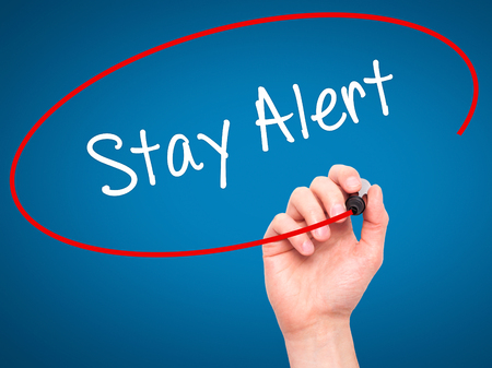 stay alert: Man Hand writing Stay Alert with black marker on visual screen. Isolated on blue. Business, technology, internet concept. Stock Photo