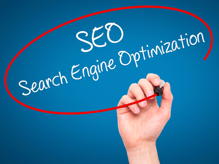 backlink: Man Hand writing SEO Search Engine Optimization with black marker on visual screen. Isolated on blue. Business, technology, internet concept. Stock Photo