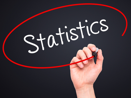regression: Man Hand writing Statistics with black marker on visual screen. Isolated on black. Business, technology, internet concept. Stock Photo Stock Photo
