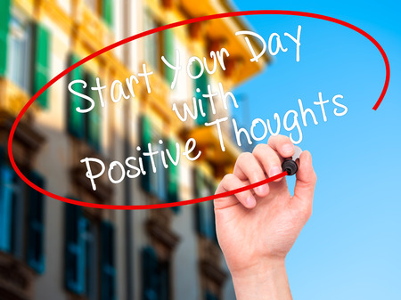 positiveness: Man Hand writing Start your Dat with Positive Thoughts with black marker on visual screen. Isolated on city. Business, technology, internet concept. Stock Photo Stock Photo