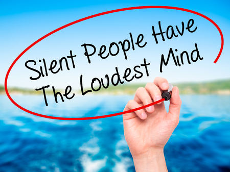 Man Hand writing Silent People Have The Loudest Mind with black marker on visual screen. Isolated on background. Business, technology, internet concept. Stock Photo