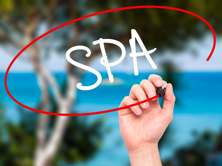 rejuvenate: Man Hand writing SPA with black marker on visual screen. Isolated on nature. Business, technology, internet concept. Stock Photo