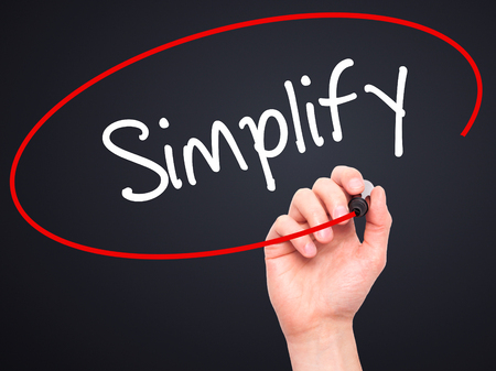 simplify: Man Hand writing Simplify with black marker on visual screen. Isolated on black. Business, technology, internet concept. Stock Photo