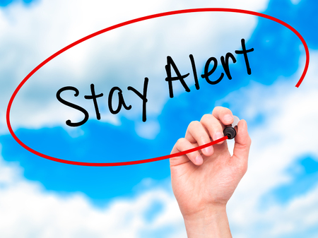 stay alert: Man Hand writing Stay Alert with black marker on visual screen. Isolated on sky. Business, technology, internet concept. Stock Photo Stock Photo