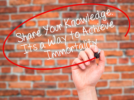 immortality: Man Hand writing Share Your Knowledge. Its a Way to Achieve Immortality with black marker on visual screen. Isolated on bricks. Business, technology, internet concept. Stock Photo