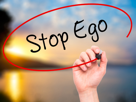 ego: Man Hand writing  Stop Ego with black marker on visual screen. Isolated on background. Business, technology, internet concept. Stock Photo