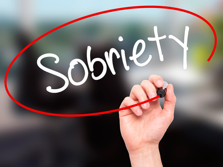 sobriety: Man Hand writing Sobriety with black marker on visual screen. Isolated on office. Business, technology, internet concept. Stock Photo