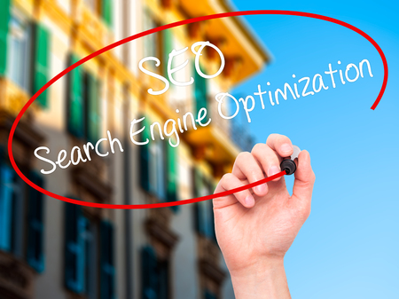 meta tags: Man Hand writing SEO Search Engine Optimization with black marker on visual screen. Isolated on city. Business, technology, internet concept. Stock Photo