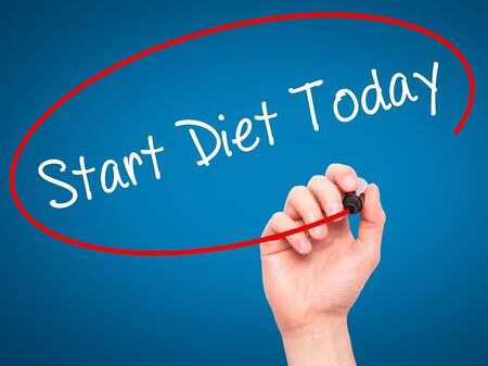 overeat: Man Hand writing Start Diet Today  with black marker on visual screen. Isolated on blue. Business, technology, internet concept. Stock Photo