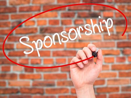 sponsorship: Man Hand writing Sponsorship  with black marker on visual screen. Isolated on bricks. Business, technology, internet concept. Stock Photo
