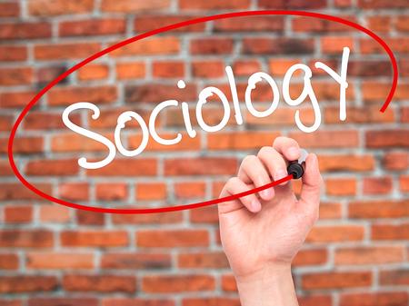 sociology: Hombre de la mano escribiendo Sociología con marcador negro en la pantalla visual. Aislado en el fondo. Negocios, la tecnología, el concepto de internet. Foto de stock