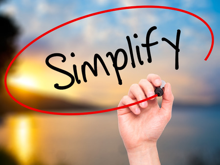 simplify: Man Hand writing Simplify with black marker on visual screen. Isolated on nature. Business, technology, internet concept. Stock Photo Stock Photo