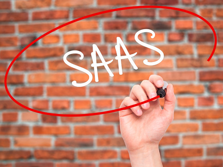 unified: Man Hand writing SAAS with black marker on visual screen. Isolated on background. Business, technology, internet concept. Stock Photo