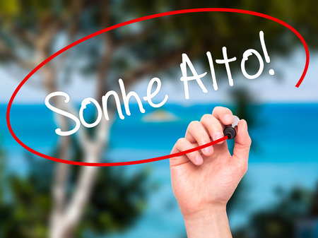 Man Hand writing Sonhe Alto! (Dream Big in Portuguese) with black marker on visual screen. Isolated on nature. Business, technology, internet concept. Stock Photo