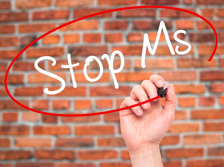 spasms: Man Hand writing Stop Ms with black marker on visual screen. Isolated on bricks. Business, technology, internet concept. Stock Photo Stock Photo