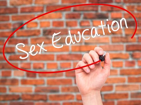 sex education: Man Hand writing Sex Education with black marker on visual screen. Isolated on bricks. Business, technology, internet concept. Stock Photo