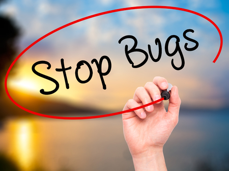 Man Hand writing Stop Bugs with black marker on visual screen. Isolated on background. Business, technology, internet concept. Stock Photo