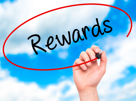 payoff: Man Hand writing Rewards with black marker on visual screen. Isolated on sky. Business, technology, internet concept. Stock Photo