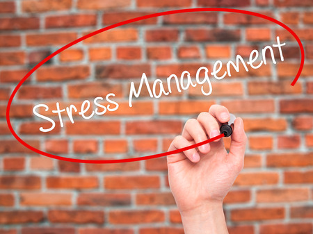 stressing: Man Hand writing Stress Management with black marker on visual screen. Isolated on bricks. Business, technology, internet concept. Stock Photo Stock Photo