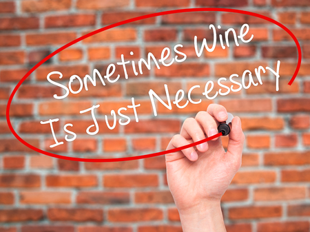 necessary: Man Hand writing Sometimes Wine Is Just Necessary with black marker on visual screen. Isolated on bricks. Business, technology, internet concept. Stock Photo Stock Photo