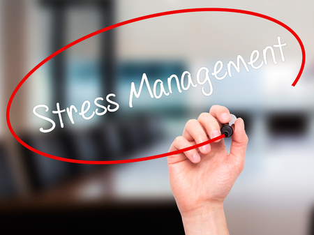 stressing: Man Hand writing Stress Management with black marker on visual screen. Isolated on office. Business, technology, internet concept. Stock Photo